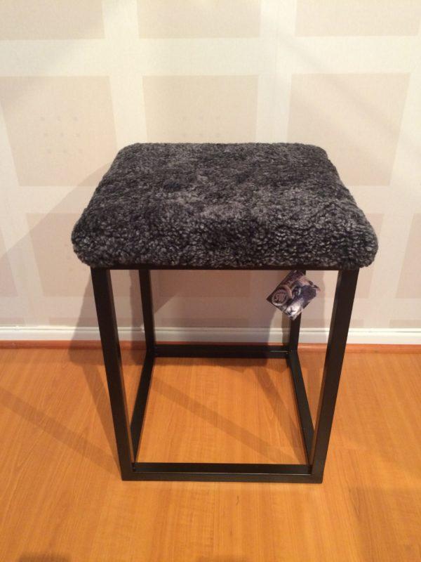 Med en underdel i metall och en dyna i fårskinn är denna pall bekväm. Välj mellan färgerna brun, grå och svart.