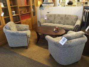 En fin soffa i grått med mönster av blommor och med trädetaljer. Soffan är just nu på rea.