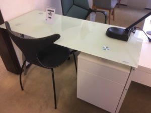 Skrivbord med bra förvaring. Skrivbordet Spic har en lucka och en låda. Skrivbordet är vitt med en skiva av glas.