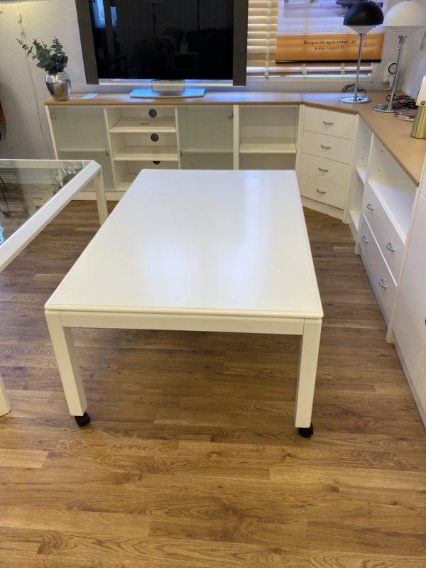 Smidigt vitlackat soffbord som lätt kan flyttas. Soffbordet är i vitlack och hjulen är svarta.