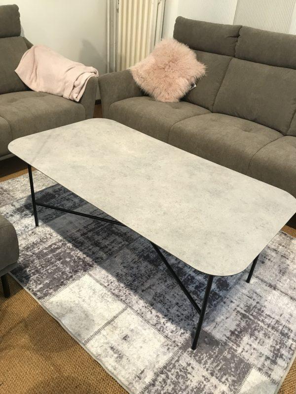 Skiva i granitgrå högtryckslaminat, det har soffbordet Fanö från Kleppe. Skivan har en sten look. Benen är i metall.