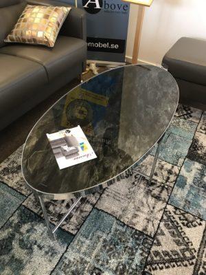Java ett soffbord från Sunsa. Detta soffbord har skiva i glas med mönster av svart marmor. Benen är i krom.